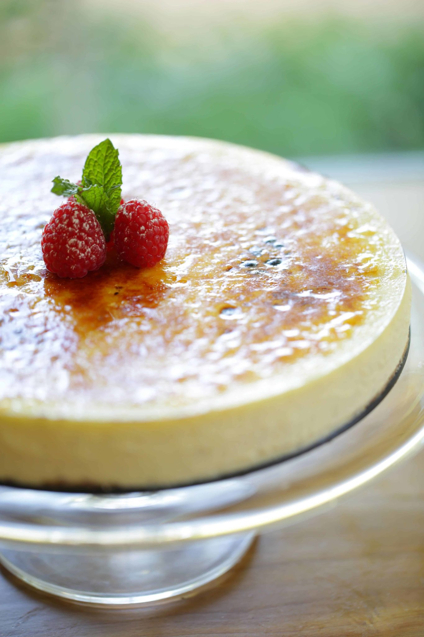 Creme Brulee Cheesecake on a cake stand with a raspberry and mint garnish