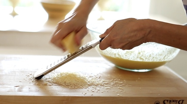 Grating fresh parmesean cheese onto a cutting board with a microplane