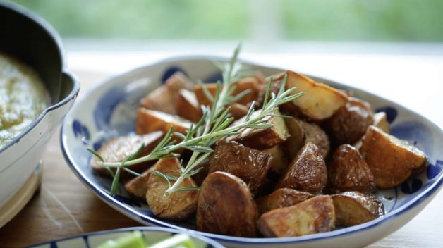A blue serving bowl with roasted potatoes and 2 fresh rosemary sprigs