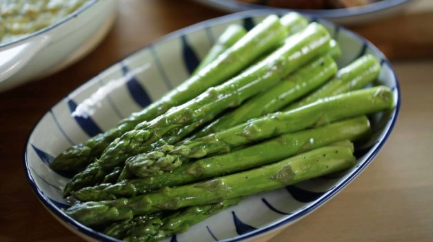 A blue and White Serving dish with a close up of roasted asparagus