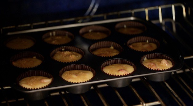 Placing strawberry muffins in the oven to bake