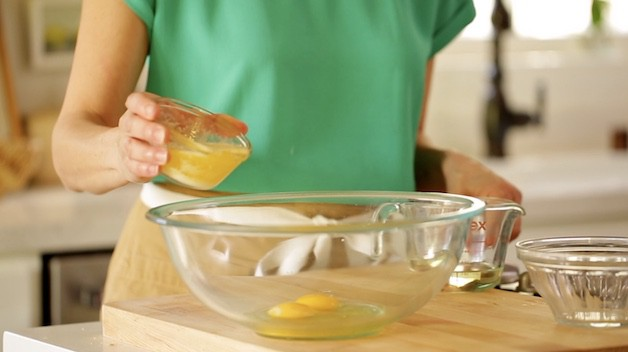 Adding melted butter to a larger mixing bowl with eggs in it