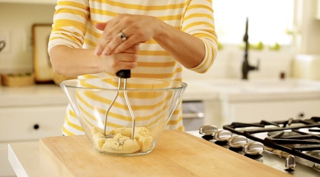 mashing bananas in a glass bowl with a potato masher