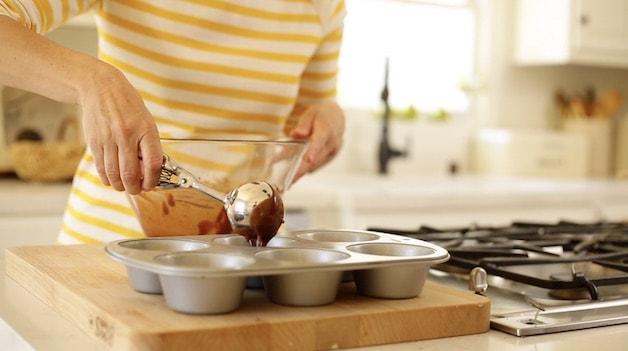 Adding chocolate batter to a jumbo muffin tin