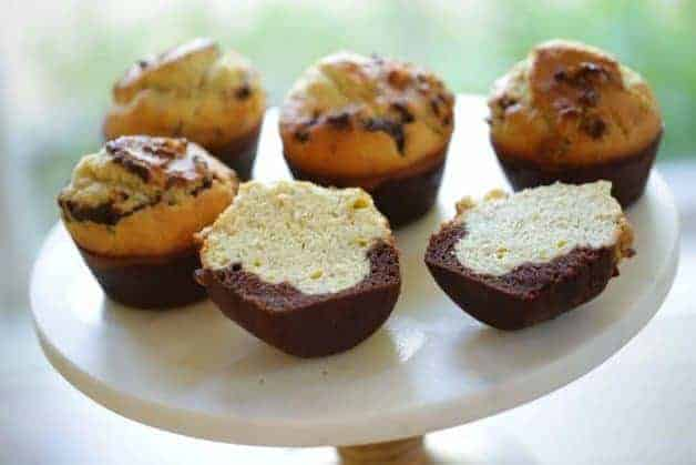 Black Bottom Banana Nut Muffins on a cake stand one sliced in half
