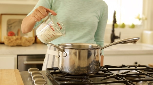 Pouring heavy cream into sauce pan