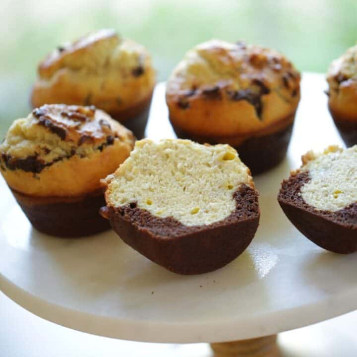 Black Bottom Banana Muffins on a cake stand sliced open