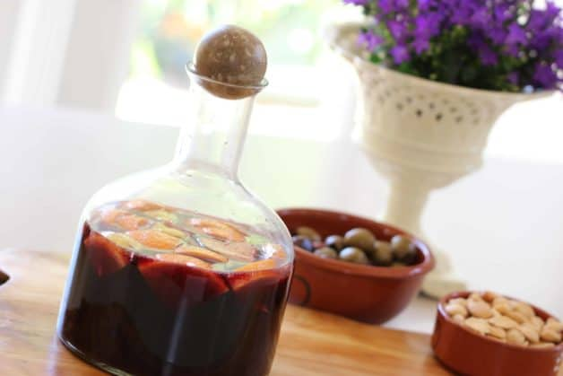 Red Wine Sangria in a decanter with olives and almonds in the background