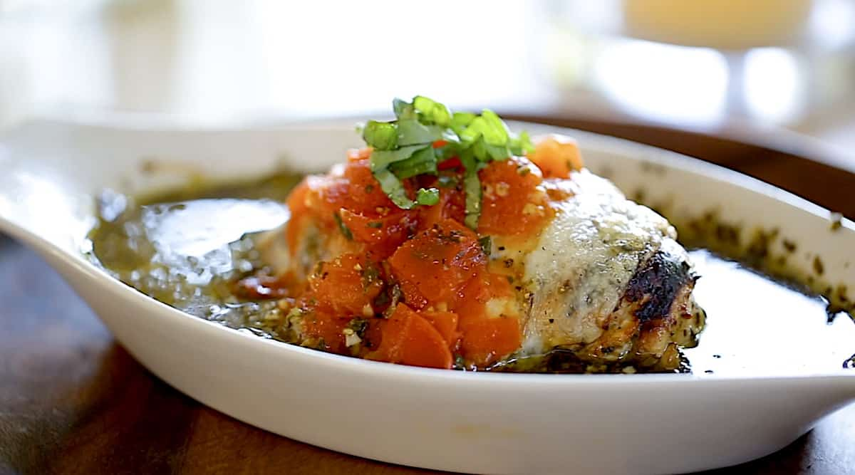 a pesto chicken bake with tomato sauce in a gratin dish