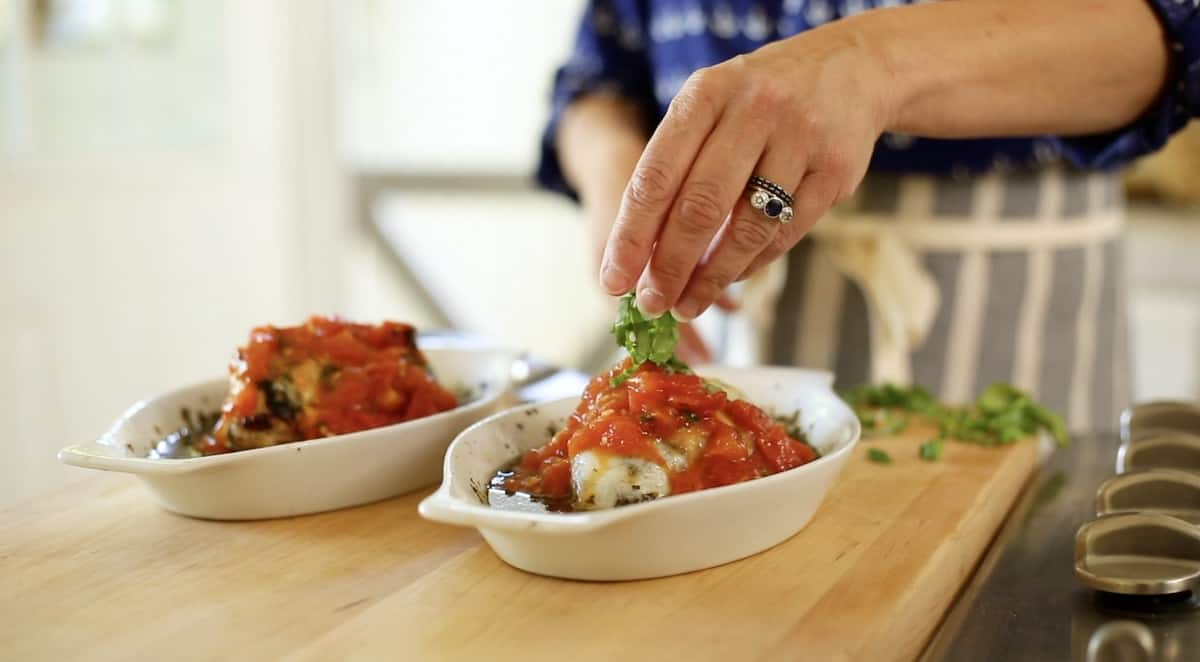 a person adding basil to the top of a pesto chicken bake