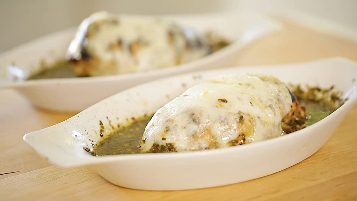 two gratin dishes with pesto sauce and chicken in it with melted mozzarella cheese on top
