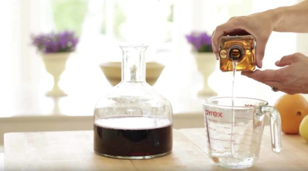 pouring cointreau into a Pyrex pitcher for an Easy Sangria Recipe