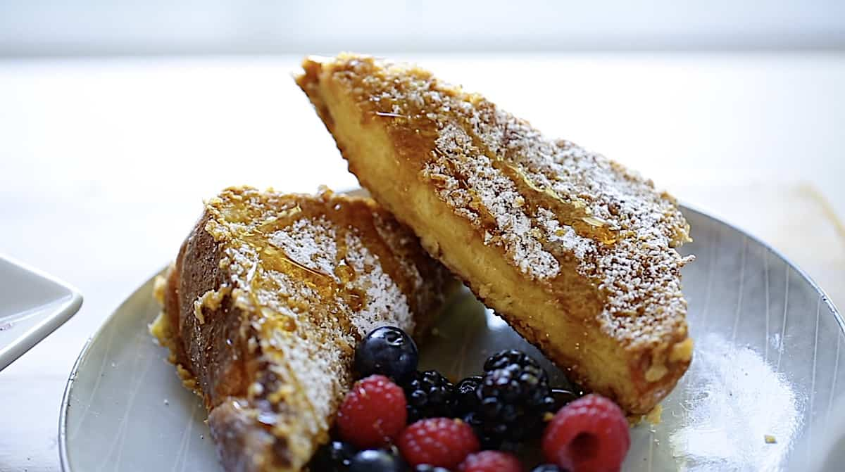 Two slices of French toast on a plate with berries and maple syrup