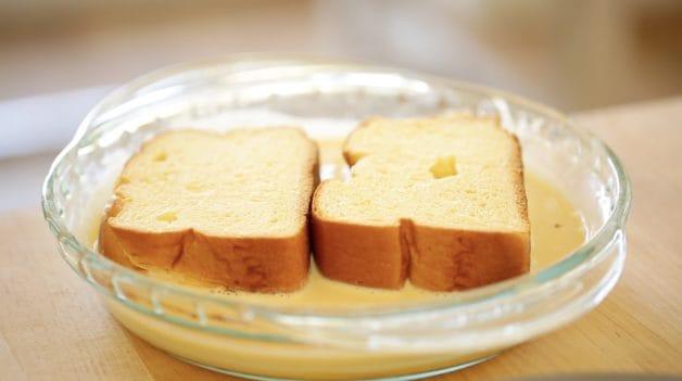 Brioche Bread soaking in egg custard for a Crunchy Brioche French Toast