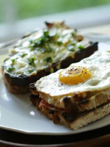 Croque Monsieur and Croque Madame Sandwiches side by side on a white plate