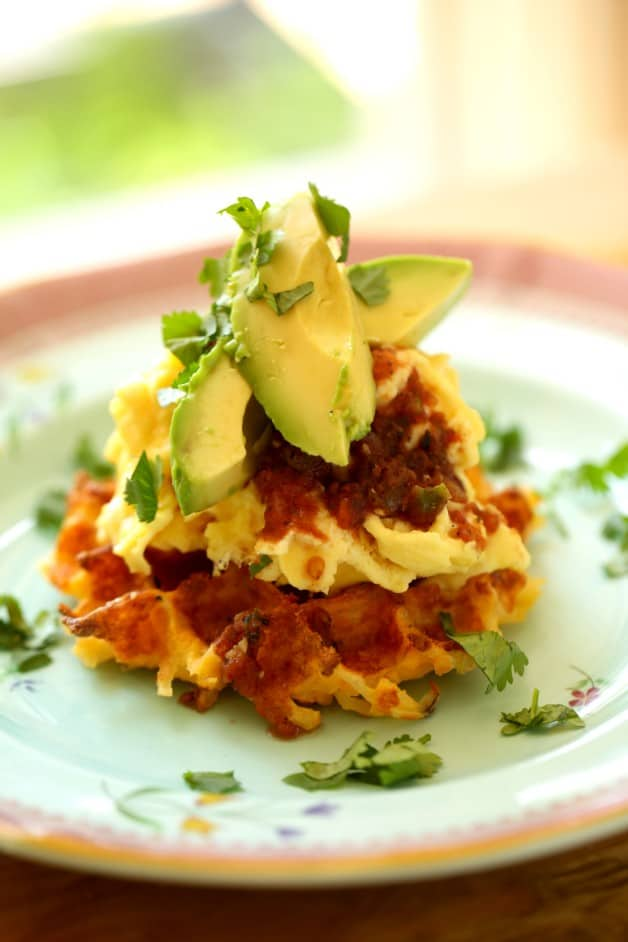 Mexican Scramble on Hash Brown Potato Waffles on plate topped with avocado zoomed in