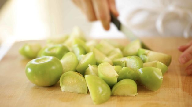 Slicing tomatillos on a cutting board for an Enchiladas Suizas Recipe