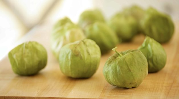 Tomatillos in their husks on a cutting board