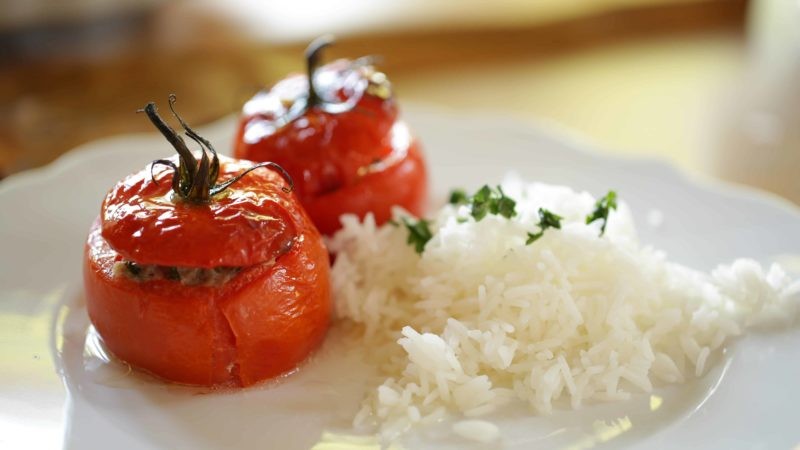 Two stuffed tomatoes on a white plate with rice and parsley