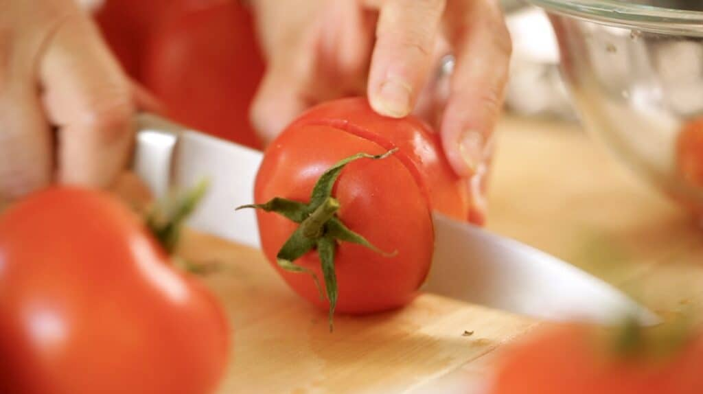 A tomato top being sliced off