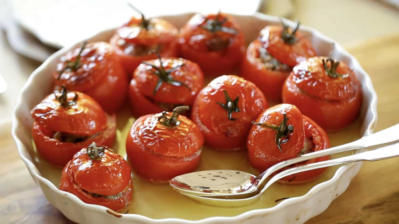 Close up of tomatoes in a white baking dish stuffed with meat