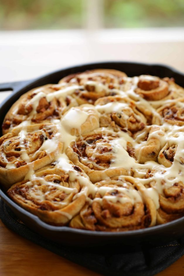 cream cheese glaze drizzled on top of overnight cinnamon rolls in a cast iron skillet