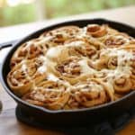 How to Make Cinnamon Rolls Recipe served in a cast iron skillet on a wood surface