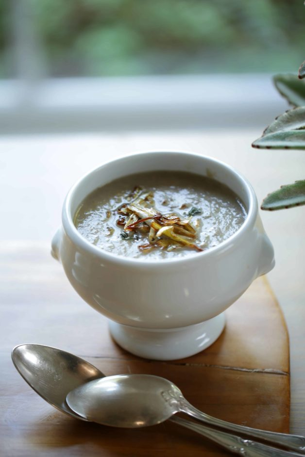Cream of Mushroom Soup topped with Crispy Leeks on a wooden board with a resting silver spoon