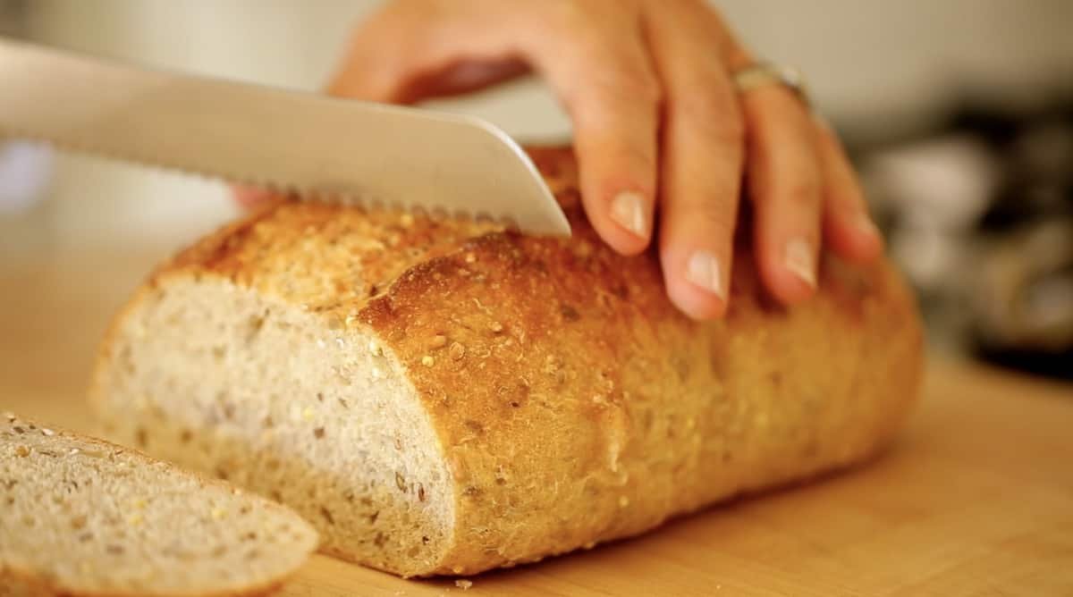 A close up of a person cutting a piece of bread