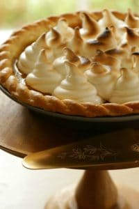 Pumpkin Pie with Marshmallow Topping on a wooden cake stand with antique pie servr