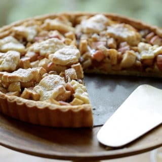 Apple Tart with Raisins and Walnuts on a cake stand with a slice taken out of it and a silver cake server