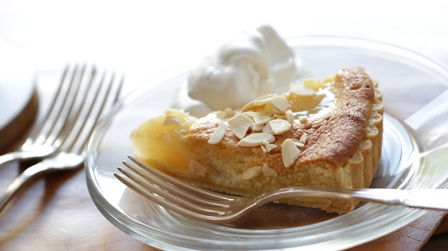 A Slice of Pear Almond Tart on a glass plate with whipped cream