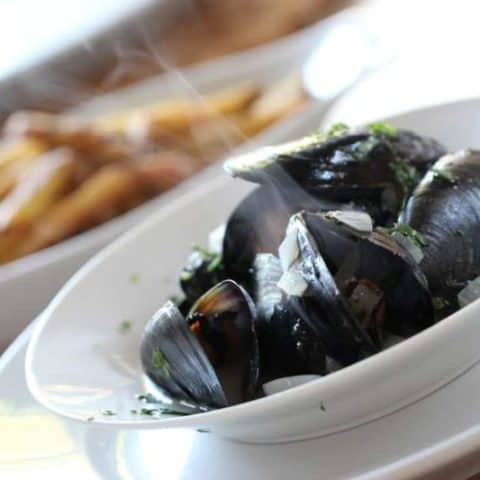 Steaming mussels garnished with parsley in a white bowl