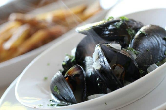 Easy Moules Frites served in separate white dishes on a wood surface