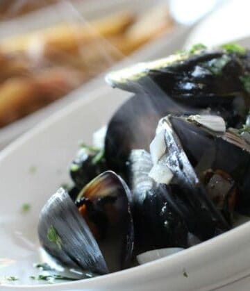 A bowl steaming mussels with french fries in the background