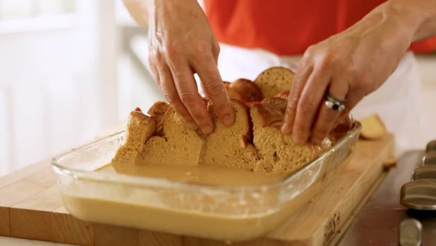 Arranging bread in casserole dish for a Gingerbread French Toast with Cinnamon Syrup Casserole