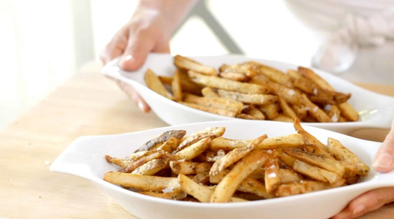 two white gratin dishes loaded with french fries