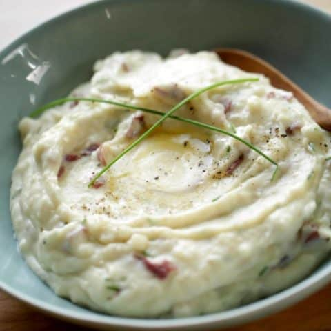 Mashed Potatoes in a blue bowl with a pool of butter, freshly cracked pepper and long chives