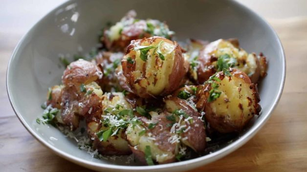 Smashed Potatoes in bowl garnished with parsley and parmesan cheese