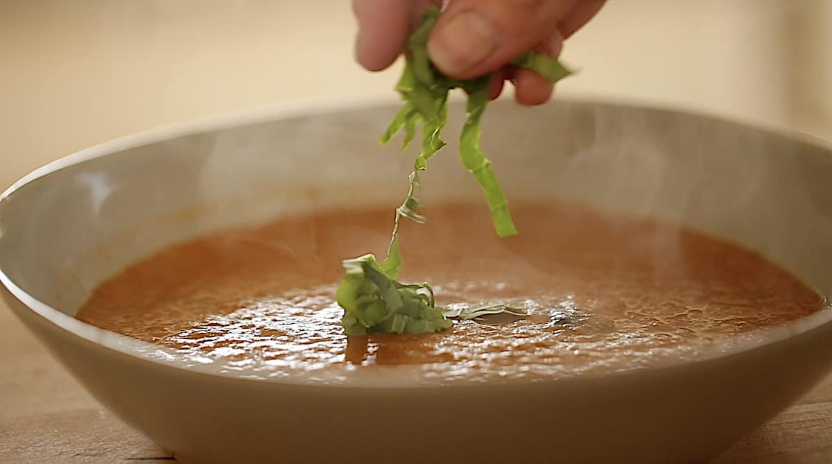 a person adding sliced basil to a roasted tomato soup