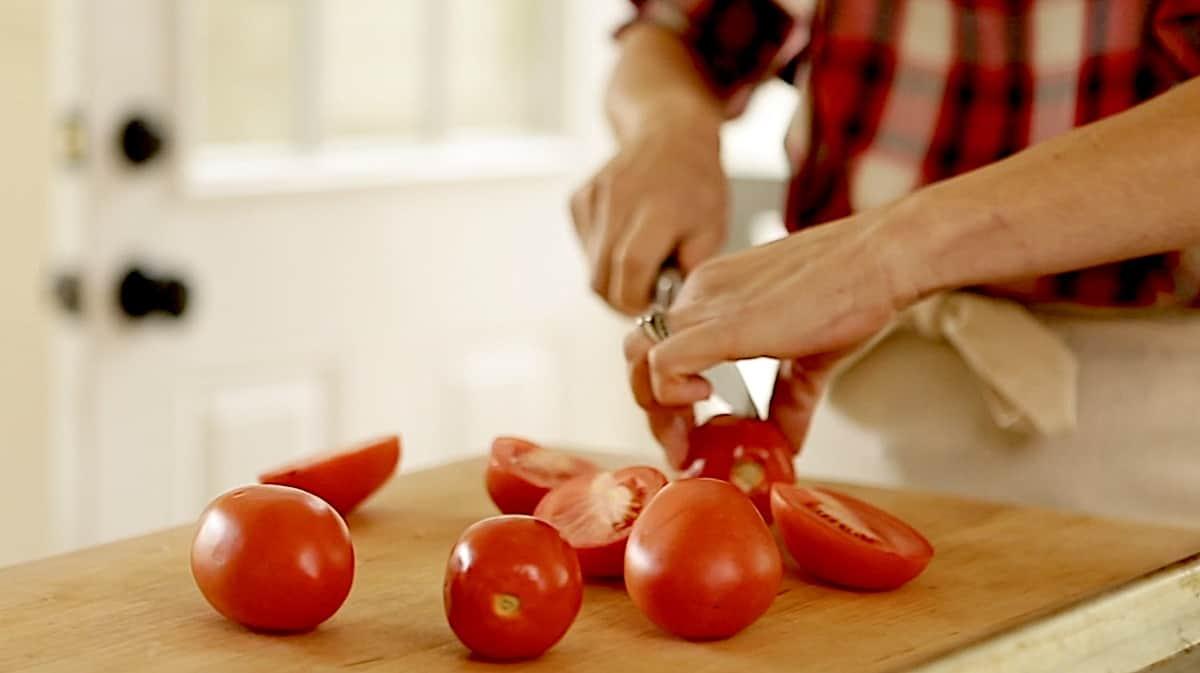 slicing a roma tomato in half