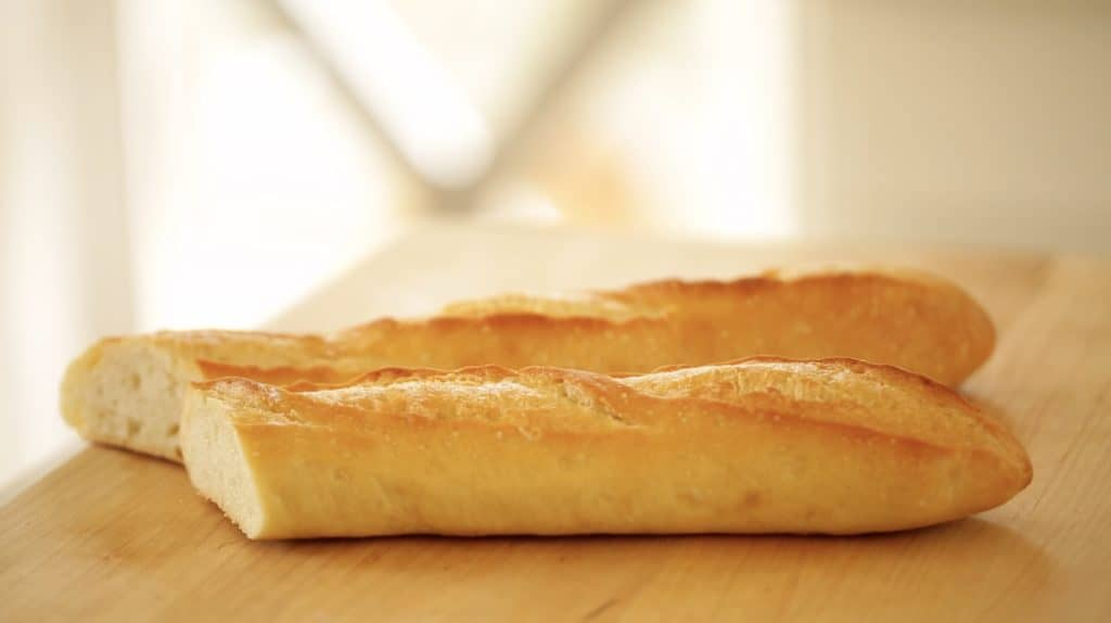 Close up shot of baguettes on cutting board about to be made into croutons