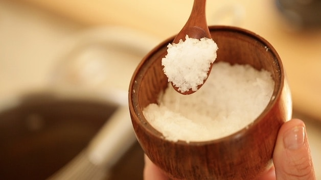fleur de sel sea salt in a wooden pot with wooden spoon