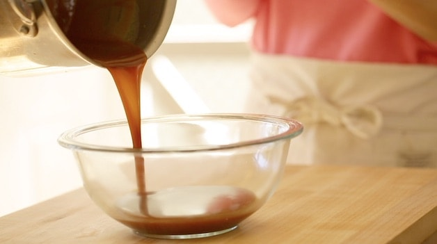 pouring caramel from a pot into a clear bowl