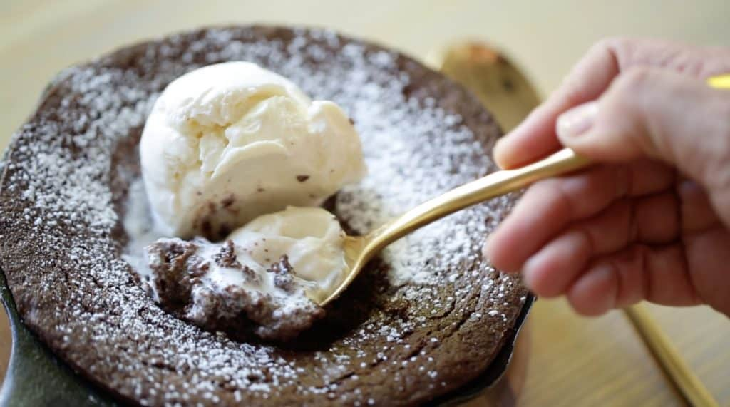 Warm Chocolate Skillet Cake with Spoon taking a bite of vanilla Ice Cream on Top