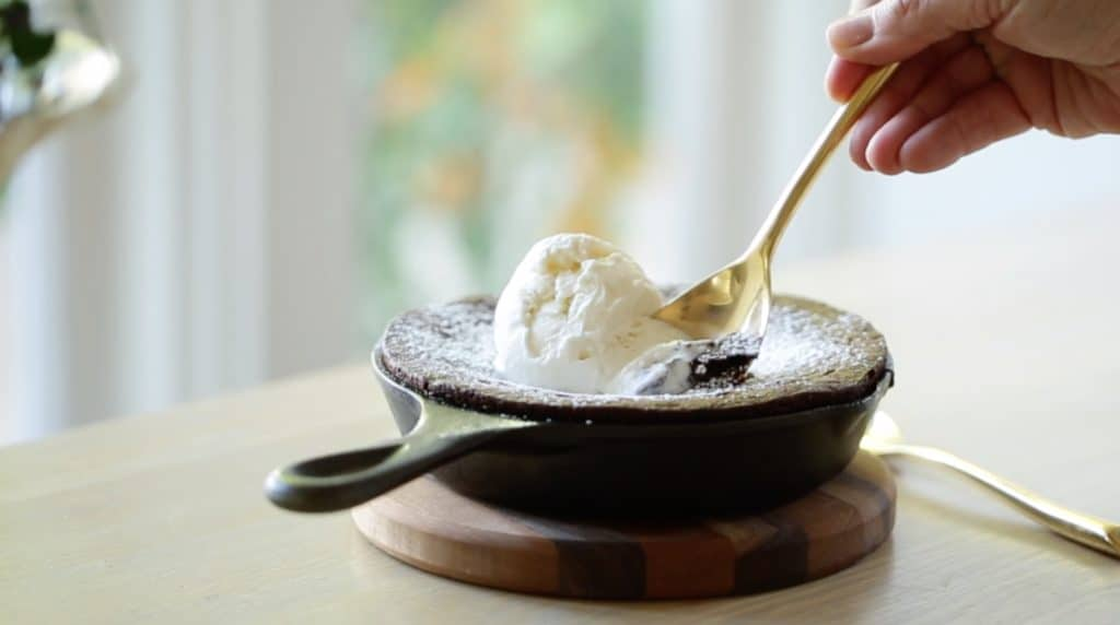 Warm Chocolate Skillet Cake with a spoon taking a bite of the scoop of vanilla ice cream on top