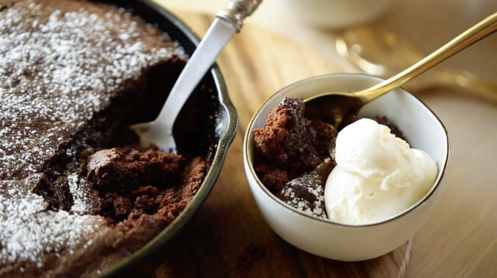 Warm chocolate skillet cake in a cast-iron skillet with a bowl of cake scooped out of it topped with vanilla ice cream