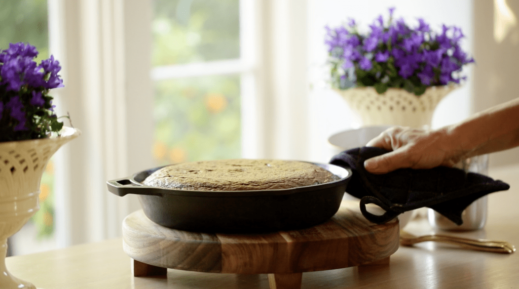 Warm Chocolate Skillet Cake in a cast-iron skillet served on a table on top of a wooden trivet