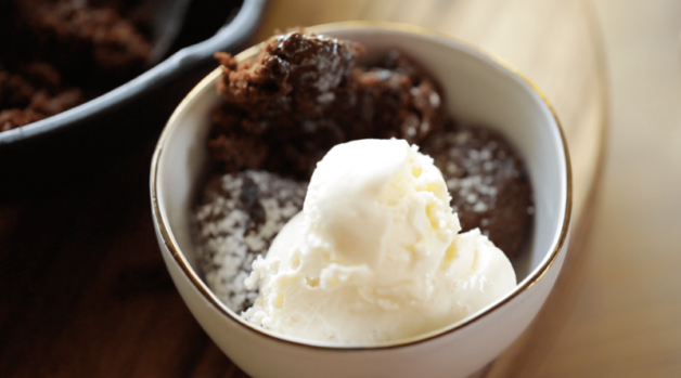 Warm Chocolate Skillet Cake in a bowl with a scoop of vanilla ice cream on top