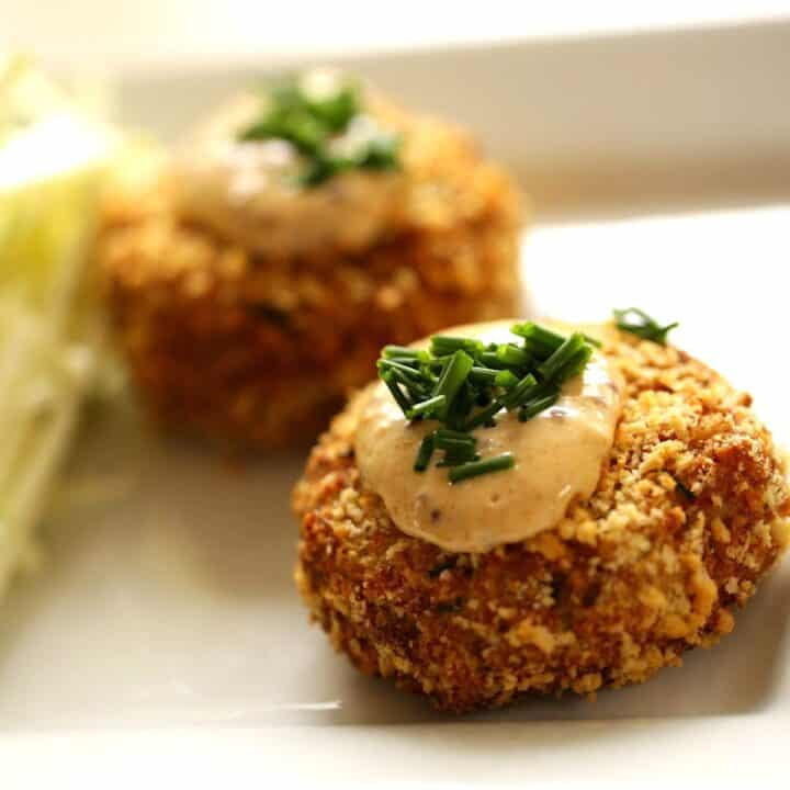 Air Fryer Crab Cakes topped with remoulade sauce and fresh chives